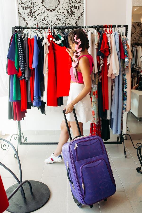 Μοντέρνο κορίτσι με την μπλε τσάντα ταξιδιού πριν από το ταξίδι, που κάνει τις αγορές στοκ εικόνες