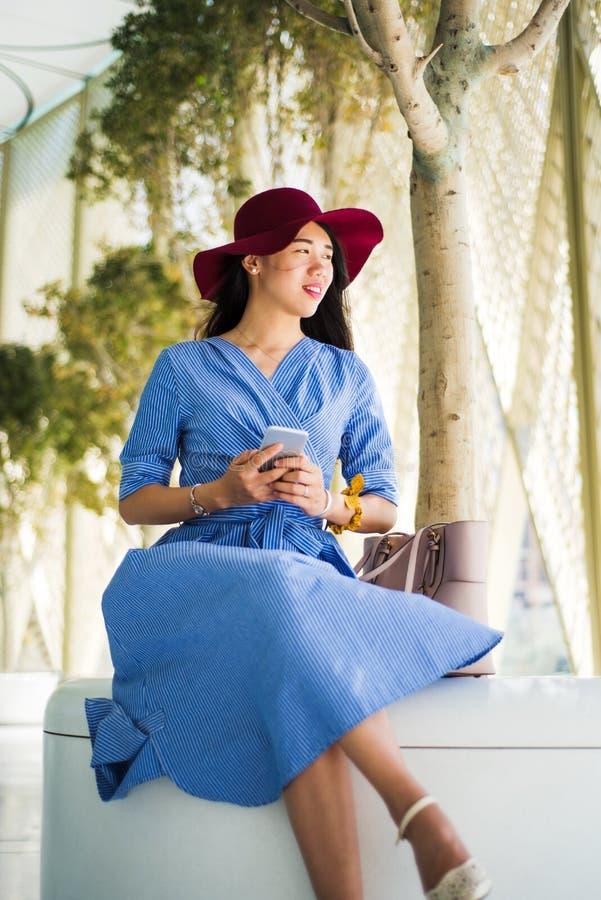 Μοντέρνο κορίτσι που φορά το μπλε φόρεμα και που κρατά ένα τηλέφωνο στοκ εικόνα με δικαίωμα ελεύθερης χρήσης