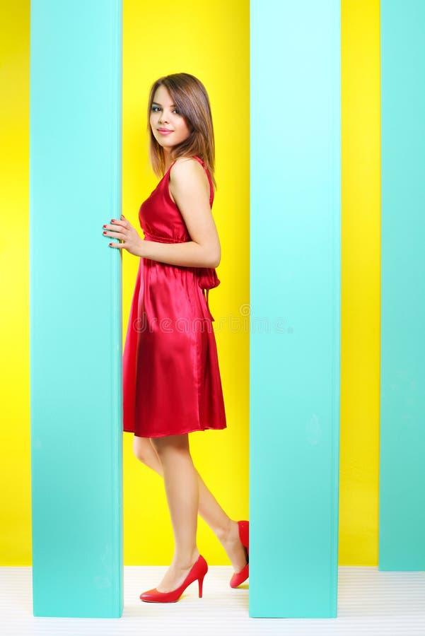 Μοντέρνο κορίτσι σε ένα κόκκινο φόρεμα στοκ φωτογραφία