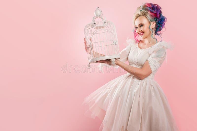 Μοντέρνο κορίτσι στο άσπρο φόρεμα Δημιουργικός χρωματισμός τρίχας Πολύχρωμο hairstyle Έννοια με ένα κενό κλουβί πουλιών στοκ φωτογραφία