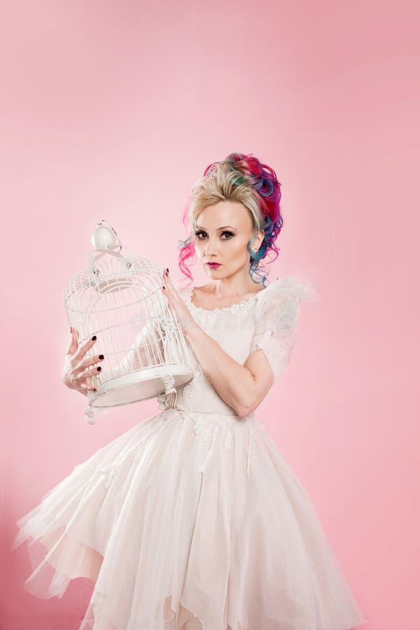 Μοντέρνο κορίτσι στο άσπρο φόρεμα Δημιουργικός χρωματισμός τρίχας Πολύχρωμο hairstyle Έννοια με ένα κενό κλουβί πουλιών στοκ φωτογραφίες με δικαίωμα ελεύθερης χρήσης