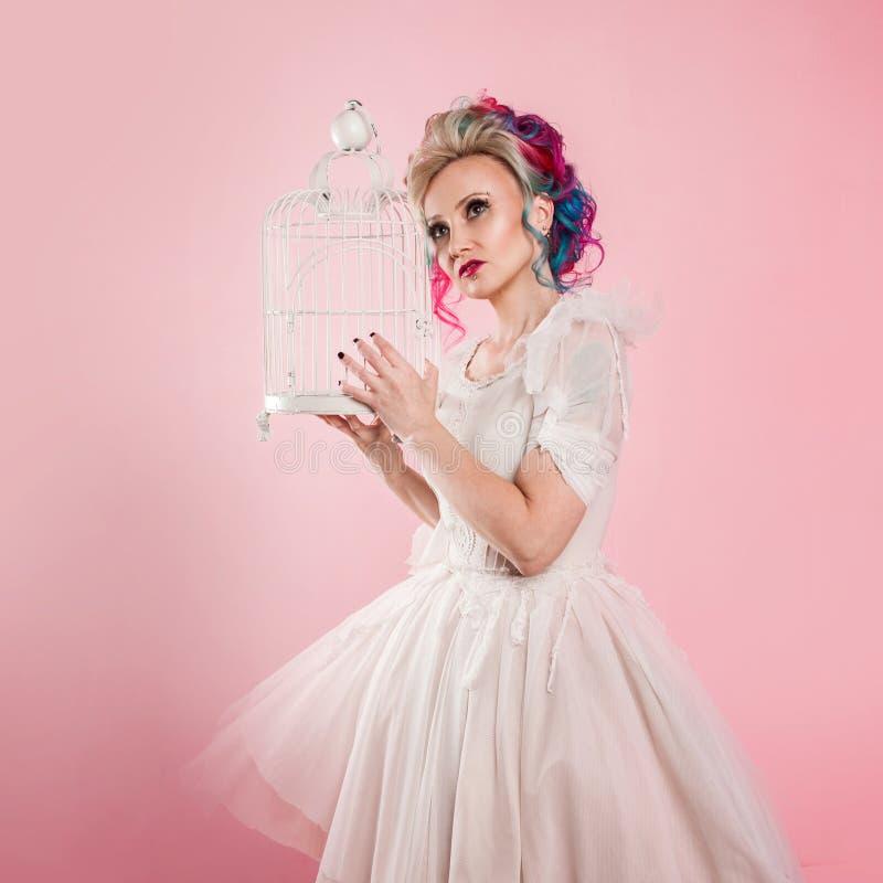 Μοντέρνο κορίτσι στο άσπρο φόρεμα Δημιουργικός χρωματισμός τρίχας Πολύχρωμο hairstyle Έννοια με ένα κενό κλουβί πουλιών στοκ φωτογραφία με δικαίωμα ελεύθερης χρήσης