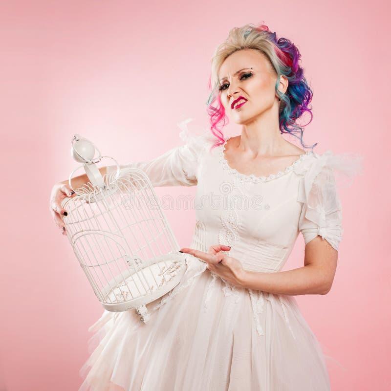 Μοντέρνο κορίτσι στο άσπρο φόρεμα Δημιουργικός χρωματισμός τρίχας Πολύχρωμο hairstyle Έννοια με ένα κενό κλουβί πουλιών στοκ εικόνα με δικαίωμα ελεύθερης χρήσης