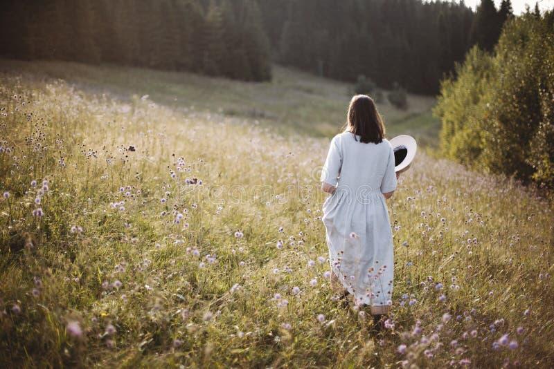 Μοντέρνο κορίτσι στο αγροτικό φόρεμα και καπέλο που περπατά μεταξύ των wildflowers στο ηλιόλουστο λιβάδι στα βουνά Χαλάρωση γυναι στοκ φωτογραφίες