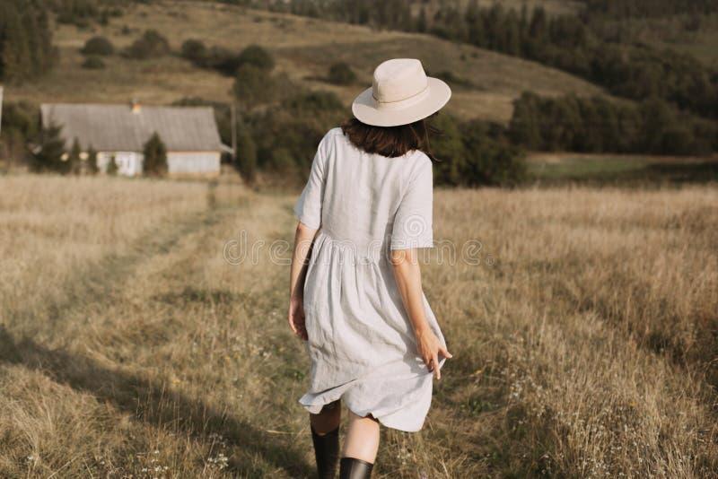 Μοντέρνο κορίτσι στο φόρεμα και το καπέλο λινού που περπατούν μεταξύ των χορταριών και wildflowers στον ηλιόλουστο τομέα στα βουν στοκ φωτογραφίες