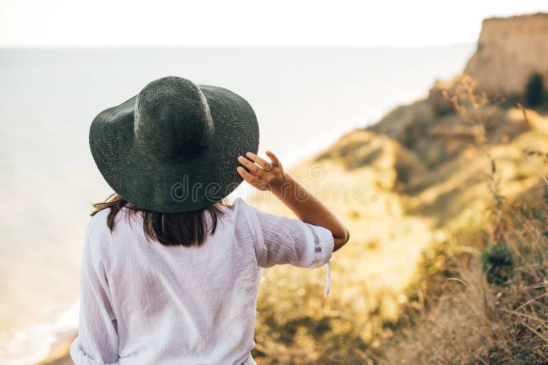 Μοντέρνο κορίτσι boho στο καπέλο που φαίνεται εν πλω στο ηλιόλουστο φως βραδιού από τον αμμώδη απότομο βράχο, πίσω άποψη Ευτυχής  στοκ εικόνα