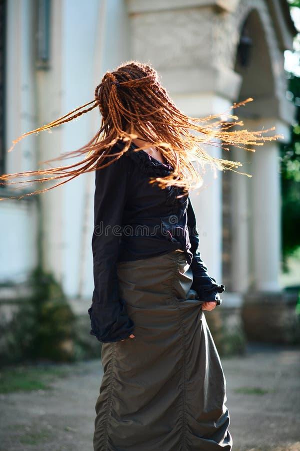 Μοντέρνο κορίτσι Dreadlocks που έχει τη διασκέδαση και επικεφαλής γρήγορο στροφών στοκ φωτογραφία