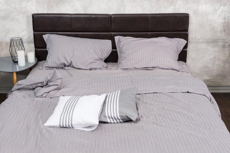 Μοντέρνο κρεβάτι με τα γκρίζα χρώματα και πίνακας πλευρών με πολλά κεριά στοκ εικόνες με δικαίωμα ελεύθερης χρήσης