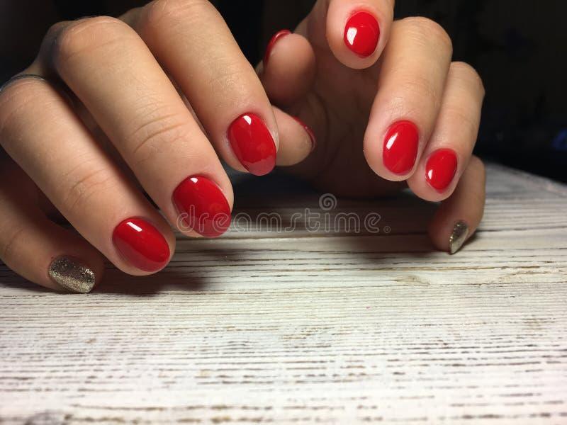 μοντέρνο κόκκινο μανικιούρ με το χρυσό σχέδιο στοκ φωτογραφία με δικαίωμα ελεύθερης χρήσης