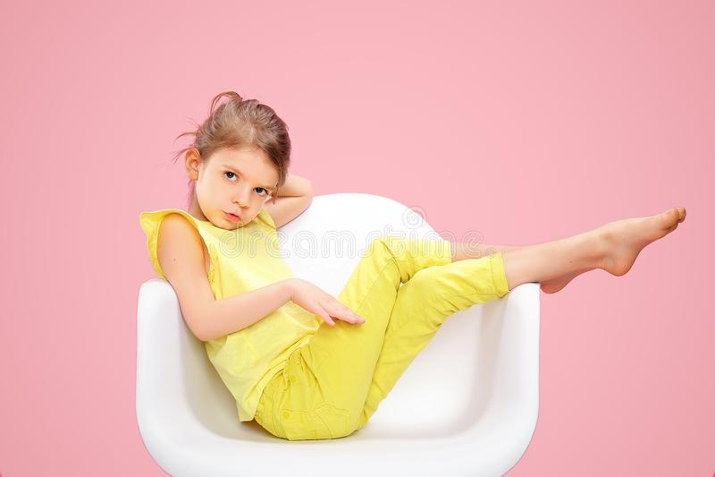Μοντέρνο μικρό κορίτσι στο κίτρινο ροζ ν στοκ φωτογραφία