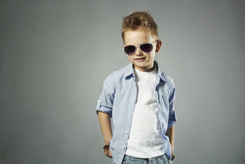 Μοντέρνο μικρό παιδί στα γυαλιά ηλίου μοντέρνο παιδί στα τζιν στοκ εικόνα