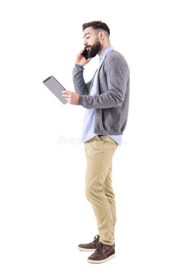 Μοντέρνο νέο ενήλικο επιχειρησιακό άτομο στο τηλέφωνο που εξετάζει τον υπολογιστή μαξιλαριών ταμπλετών στοκ φωτογραφία με δικαίωμα ελεύθερης χρήσης