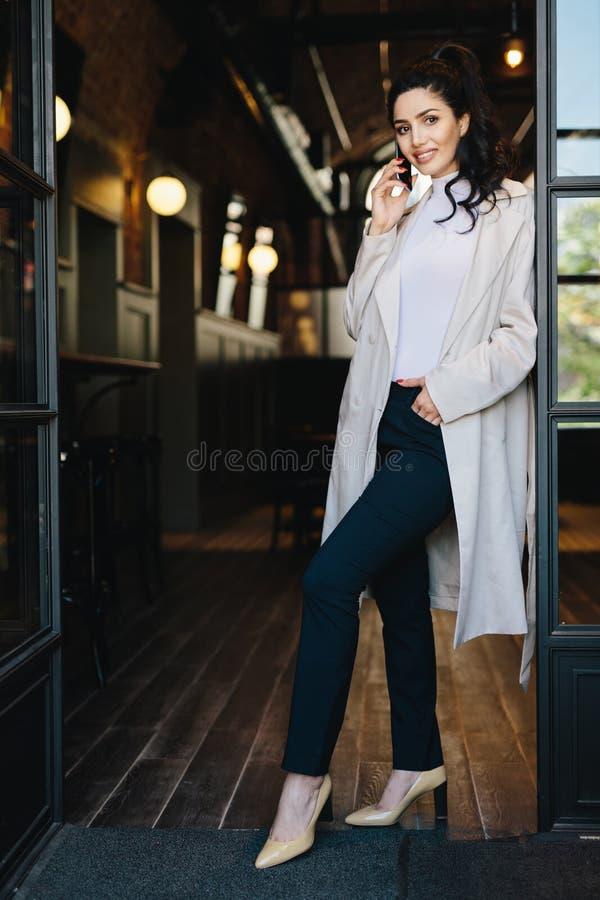 Μοντέρνο νέο θηλυκό με τη σκοτεινή τρίχα που φορά το άσπρο παλτό, μαύρο TR στοκ εικόνες με δικαίωμα ελεύθερης χρήσης