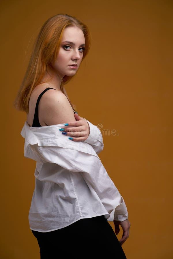 Μοντέρνο νέο κορίτσι με τη σγουρή τρίχα, που χαμογελά cutely, που θέτει, στο κίτρινο υπόβαθρο στοκ φωτογραφίες