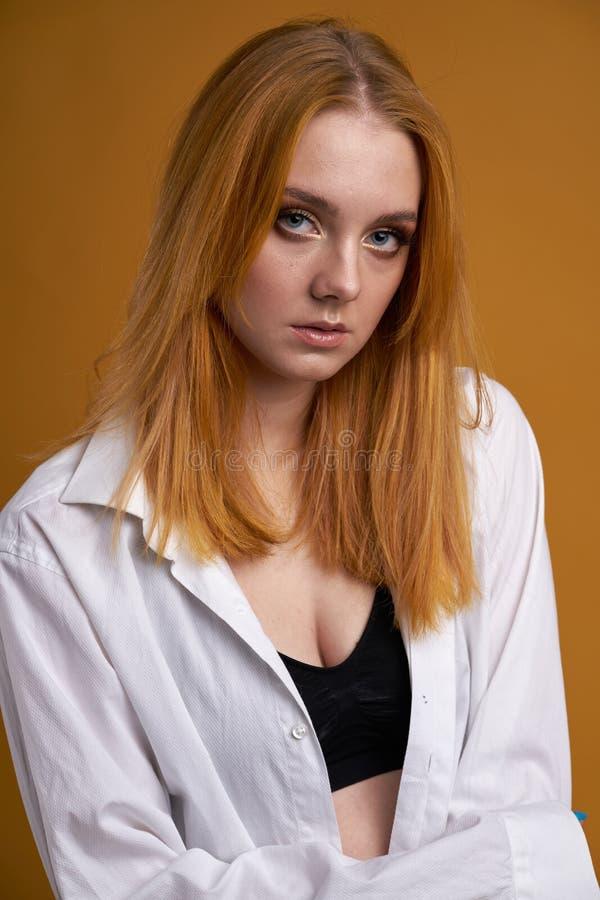 Μοντέρνο νέο κορίτσι με τη σγουρή τρίχα, που χαμογελά cutely, που θέτει, στο κίτρινο υπόβαθρο στοκ εικόνες