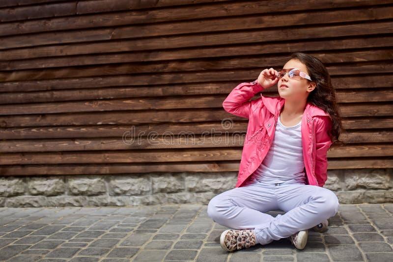 Μοντέρνο παιδί μικρών κοριτσιών που φορά ένα ρόδινο σακάκι καλοκαιριού ή φθινοπώρου, άσπρα τζιν, γυαλιά ηλίου στοκ εικόνες