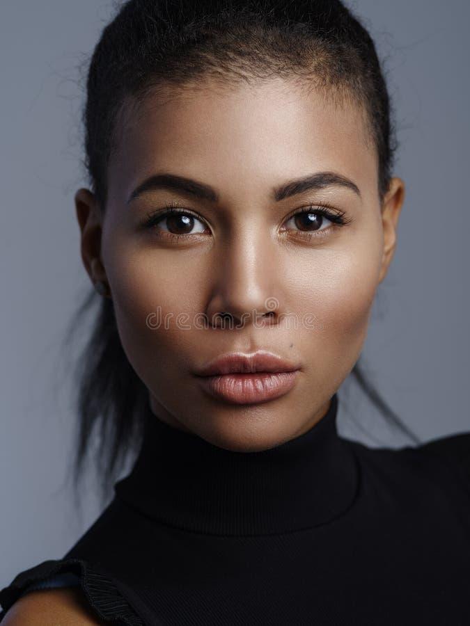 Μοντέρνο πορτρέτο κινηματογραφήσεων σε πρώτο πλάνο ενός όμορφου θηλυκού προτύπου αφροαμερικάνων με το nude φρέσκο makeup στοκ φωτογραφία