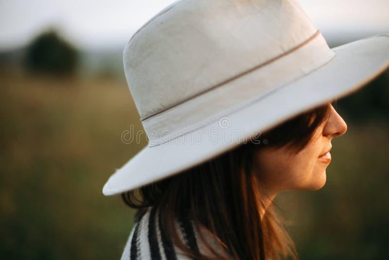 Μοντέρνο πορτρέτο κοριτσιών boho στο ηλιόλουστο φως στο ατμοσφαιρικό ηλιοβασίλεμα στο λιβάδι Ήρεμη γυναίκα hipster poncho και καπ στοκ εικόνες