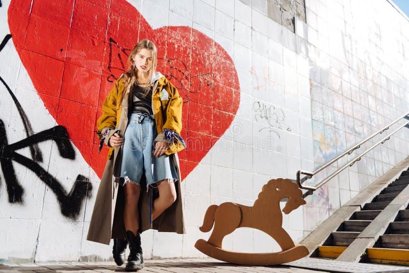 Μοντέρνο πρότυπο που φορά τα φαρδιά σορτς τζιν και το υπεργέθες παλτό στοκ εικόνα