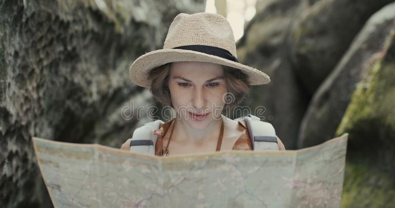 μοντέρνο ταξιδιωτικό κορίτσι στο καπέλο που εξετάζει το χάρτη, που εξερευνά τα ξύλα στοκ εικόνες
