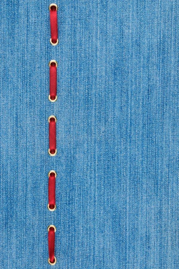 Μοντέρνο υπόβαθρο, κόκκινη κορδέλλα σατέν που παρεμβάλλεται στο τζιν στοκ φωτογραφία