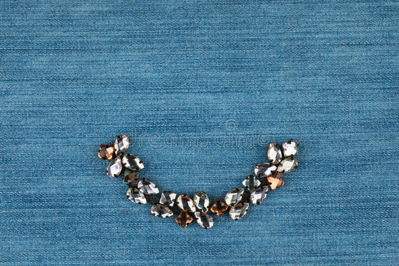 Μοντέρνο υπόβαθρο, κόσμημα με τα rhinestones που βρίσκονται στο τζιν στοκ εικόνα με δικαίωμα ελεύθερης χρήσης