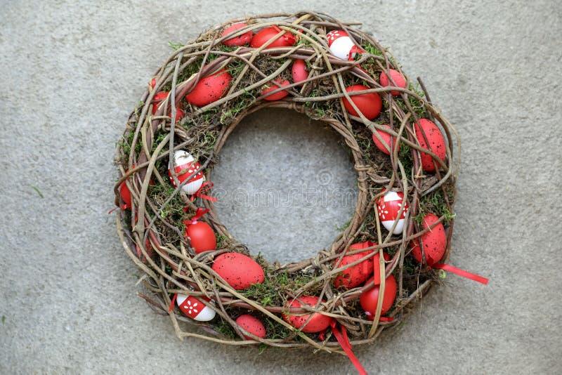 Μοντέρνο χειροποίητο στεφάνι ντεκόρ διακοπών Πάσχας των κόκκινων αυγών που στρίβονται των ξηρών κλαδίσκων και του βρύου για τη δι στοκ φωτογραφία