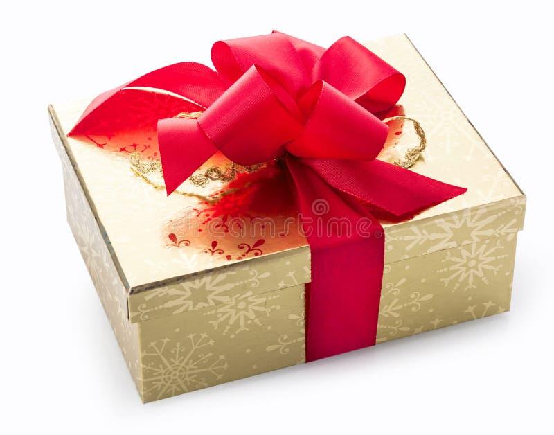 Μοντέρνο χρυσό δώρο με ένα κόκκινο διακοσμητικό τόξο στοκ φωτογραφία με δικαίωμα ελεύθερης χρήσης