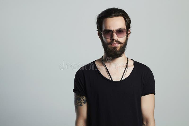 Μοντέρνο όμορφο άτομο Βάναυσο γενειοφόρο προκλητικό αγόρι στα καθιερώνοντα τη μόδα γυαλιά στοκ φωτογραφία