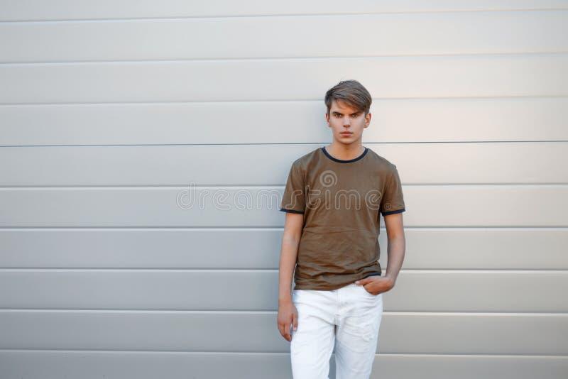 Μοντέρνο όμορφο άτομο σε μια μπλούζα και λευκά εσώρουχα κοντά σε έναν γκρίζο στοκ φωτογραφίες με δικαίωμα ελεύθερης χρήσης