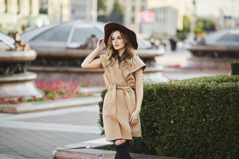 Μοντέρνο όμορφο και αισθησιακό ξανθό πρότυπο κορίτσι στο αμάνικο παλτό που ρυθμίζει το μοντέρνο καπέλο της, που χαμογελά και που  στοκ εικόνα