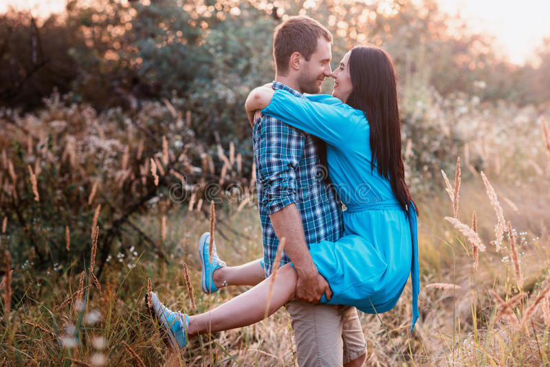 Μοντέρνο όμορφο νέο ζεύγος που στέκεται υπαίθρια στο φως ηλιοβασιλέματος στοκ εικόνες