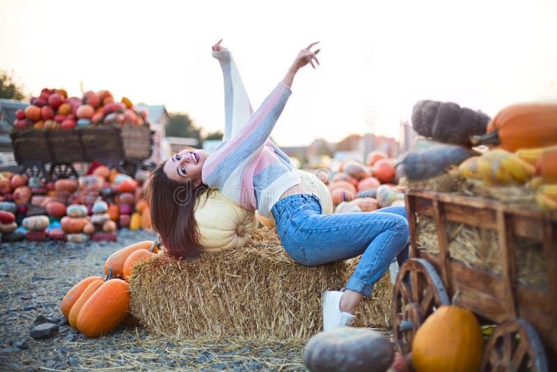 Μοντέρνο όμορφο νέο κορίτσι στο υπόβαθρο μπαλωμάτων κολοκύθας φθινοπώρου Κατοχή της διασκέδασης και τοποθέτηση στοκ εικόνες
