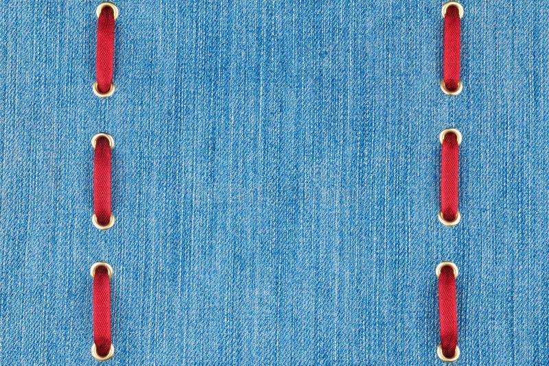 Μοντέρνο όμορφο υπόβαθρο, κόκκινη κορδέλλα σατέν που παρεμβάλλεται στο τζιν, με το διάστημα για τη δημιουργικότητά σας στοκ φωτογραφία με δικαίωμα ελεύθερης χρήσης