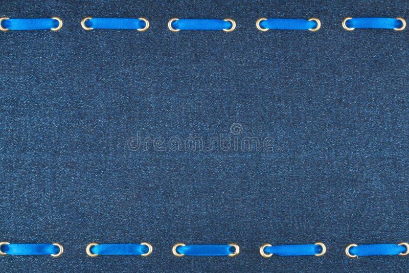 Μοντέρνο όμορφο υπόβαθρο, μπλε κορδέλλα σατέν που παρεμβάλλεται στο ύφασμα τζιν στοκ φωτογραφία με δικαίωμα ελεύθερης χρήσης