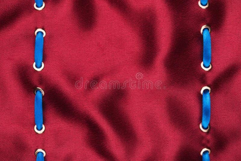 Μοντέρνο όμορφο υπόβαθρο, μπλε κορδέλλα σατέν που παρεμβάλλεται στο κόκκινο ύφασμα σατέν στοκ φωτογραφίες με δικαίωμα ελεύθερης χρήσης