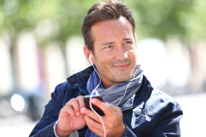 Μοντέρνο ώριμο άτομο με τα ακουστικά στοκ φωτογραφίες