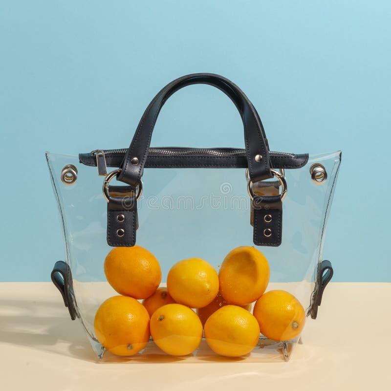 Μοντέρνο women&#x27 του s τσάντα που γεμίζουν διαφανής με τα λεμόνια Δημιουργική minimalistic έννοια στοκ εικόνες με δικαίωμα ελεύθερης χρήσης