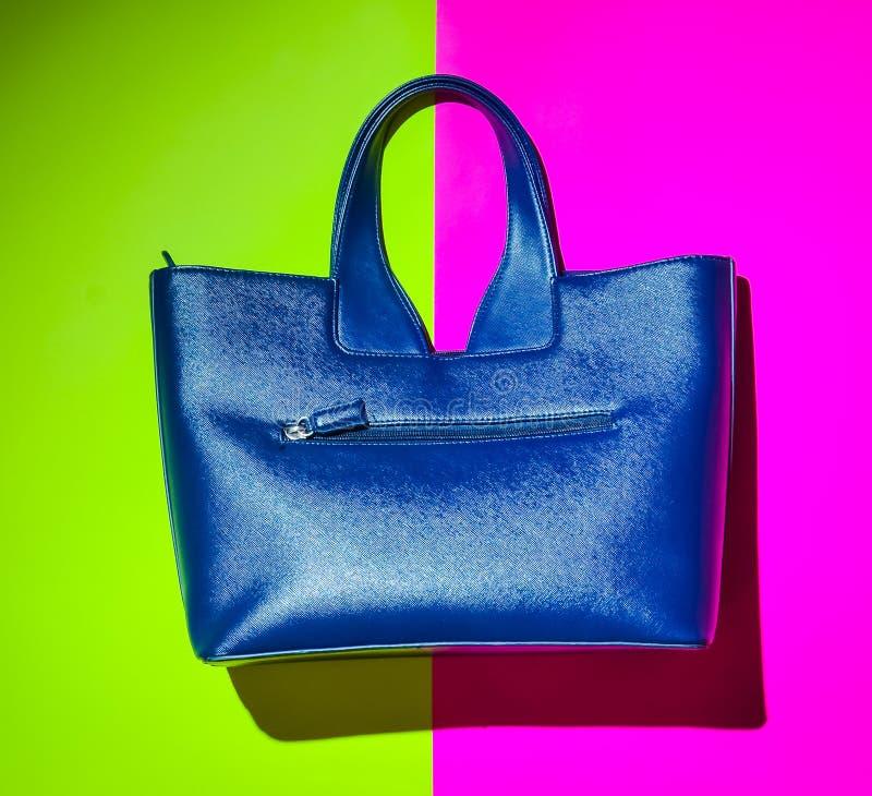 Μοντέρνο women& x27 τσάντα δέρματος του s σε ένα πράσινο ρόδινο υπόβαθρο νέου Λαϊκό φως στοκ εικόνες