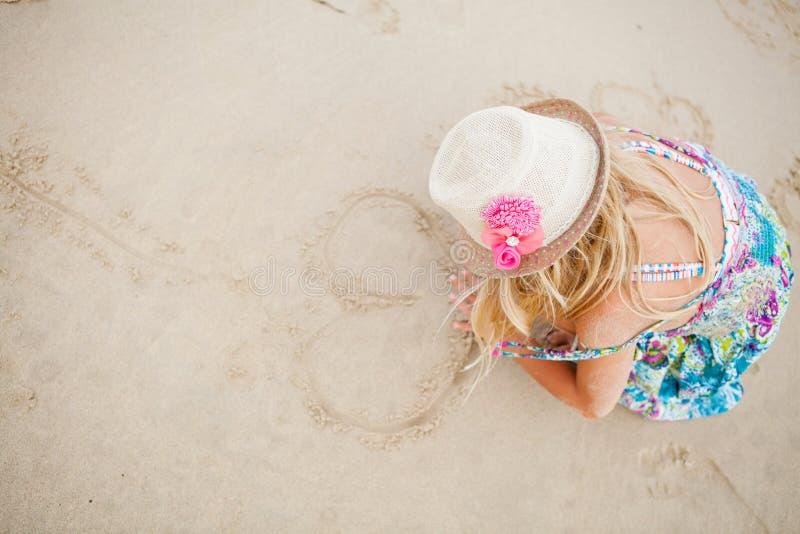 Μορφές καρδιών σχεδίων νέων κοριτσιών στην άμμο στοκ εικόνες