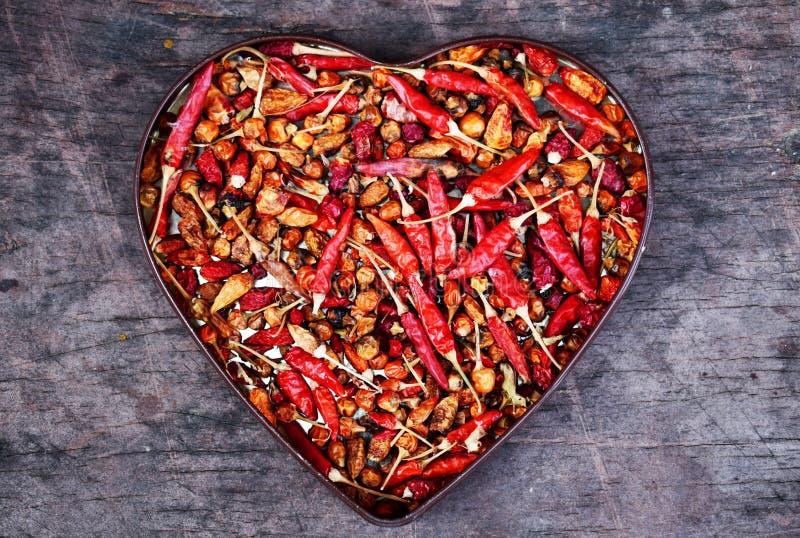 Μορφή καρδιών κόκκινων πιπεριών στο παλαιό ξύλινο γραφείο στοκ φωτογραφία με δικαίωμα ελεύθερης χρήσης