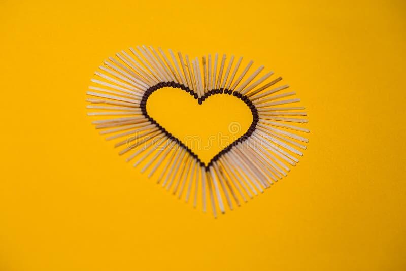 Μορφή καρδιών της αγάπης από τις αντιστοιχίες σε ένα κίτρινο υπόβαθρο στοκ εικόνες με δικαίωμα ελεύθερης χρήσης