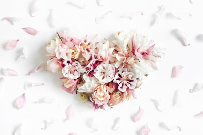 Μορφή καρδιών φιαγμένη από λουλούδια στο άσπρο υπόβαθρο στοκ εικόνες