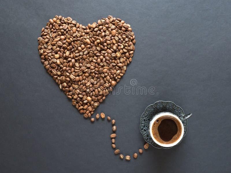 Μορφή καρδιών φιαγμένη από φασόλια καφέ και φλυτζάνι του μαύρου καφέ στο μαύρο υπόβαθρο στοκ εικόνα