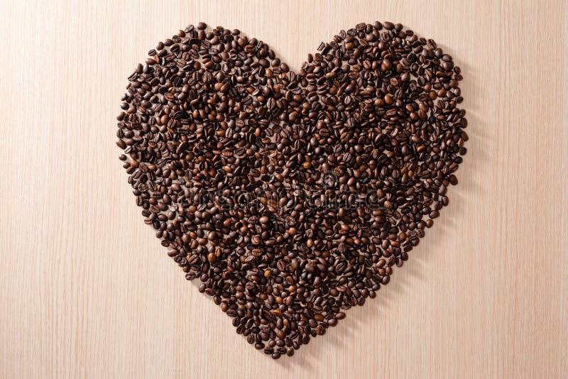 Μορφή καρδιών φιαγμένη από φασόλια καφέ στο ξύλινο υπόβαθρο στοκ εικόνα