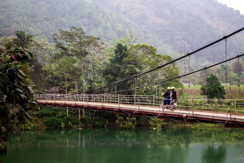 Μοτοσικλέτα σε μια γέφυρα πέρα από έναν ποταμό που περιβάλλεται από την πράσινη ζούγκλα στοκ εικόνες