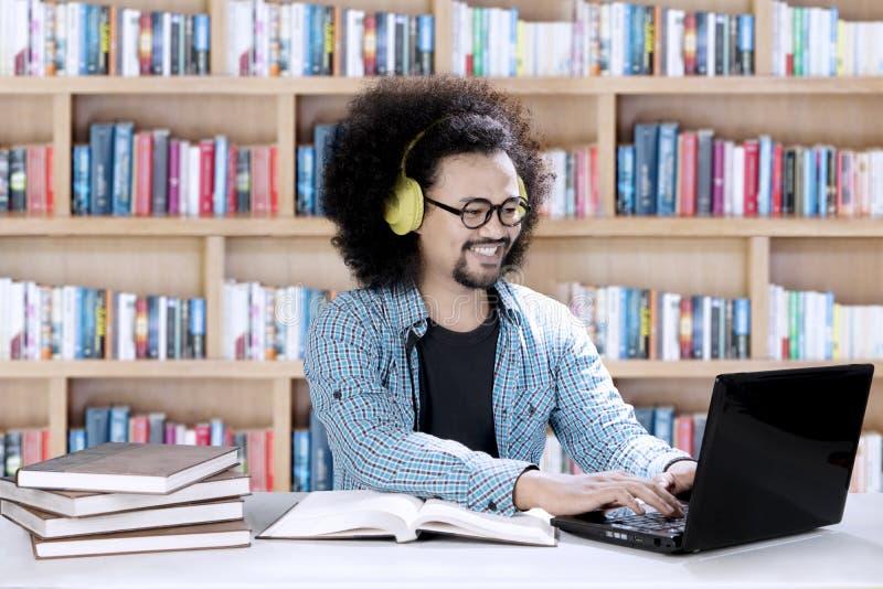 Μουσική ακούσματος ανδρών σπουδαστών στη βιβλιοθήκη στοκ φωτογραφίες με δικαίωμα ελεύθερης χρήσης