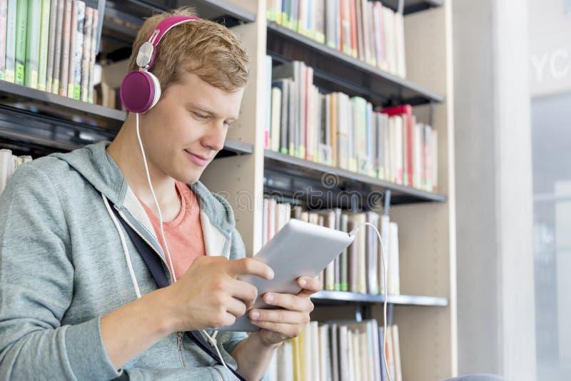 Μουσική ακούσματος ατόμων χαμόγελου στην ψηφιακή ταμπλέτα ενάντια στο ράφι στη βιβλιοθήκη στοκ φωτογραφίες