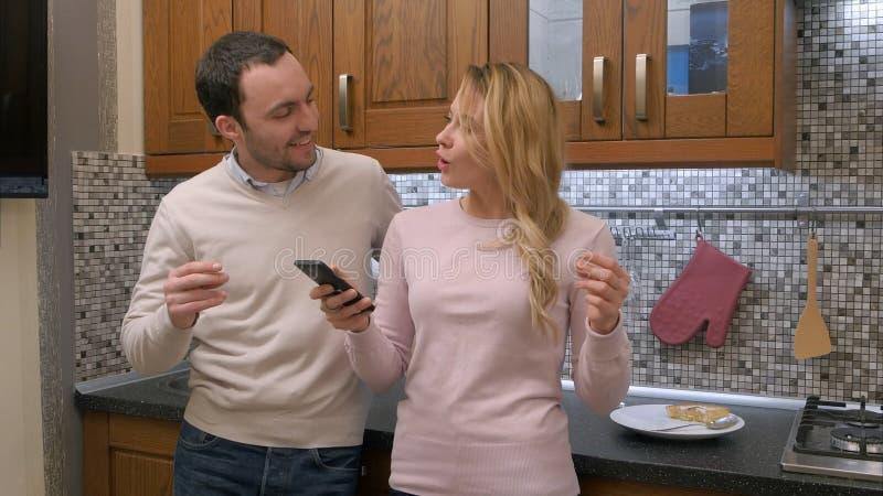 Μουσική ακούσματος ζεύγους μαζί και τραγούδι στην κουζίνα, που χορεύει από κοινού στοκ εικόνες με δικαίωμα ελεύθερης χρήσης