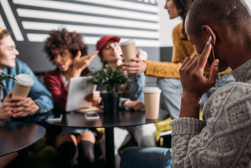 μουσική ακούσματος νεαρών άνδρων με τα ακουστικά ενώ οι φίλοι του θόλωσαν τη συνεδρίαση στοκ φωτογραφία με δικαίωμα ελεύθερης χρήσης